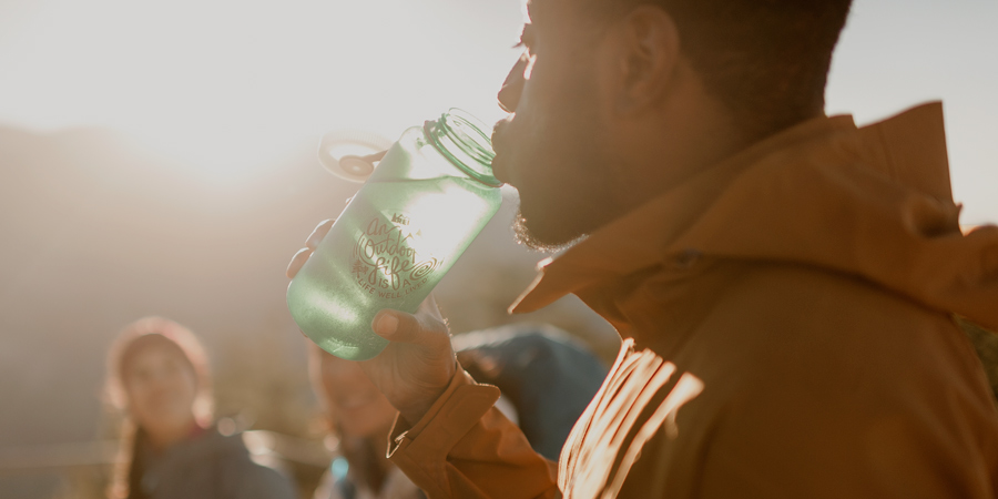 a hiker drinking from a water bottle