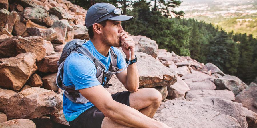 a hiker taking a hydration break on the trail