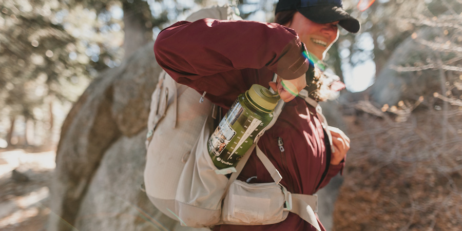 a hiker reaching for an easily accessible water bottle