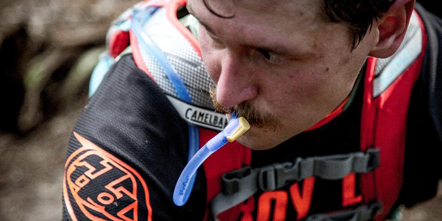 a sweaty biker drinking from the hose of hydration reservoir