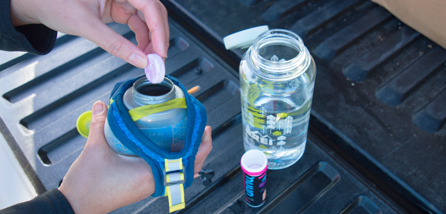 trail runner placing an electrolyte tablet into their water bottle