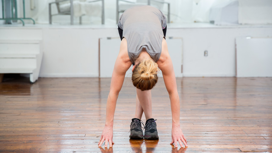 an exerciser doing a forward fold stretch