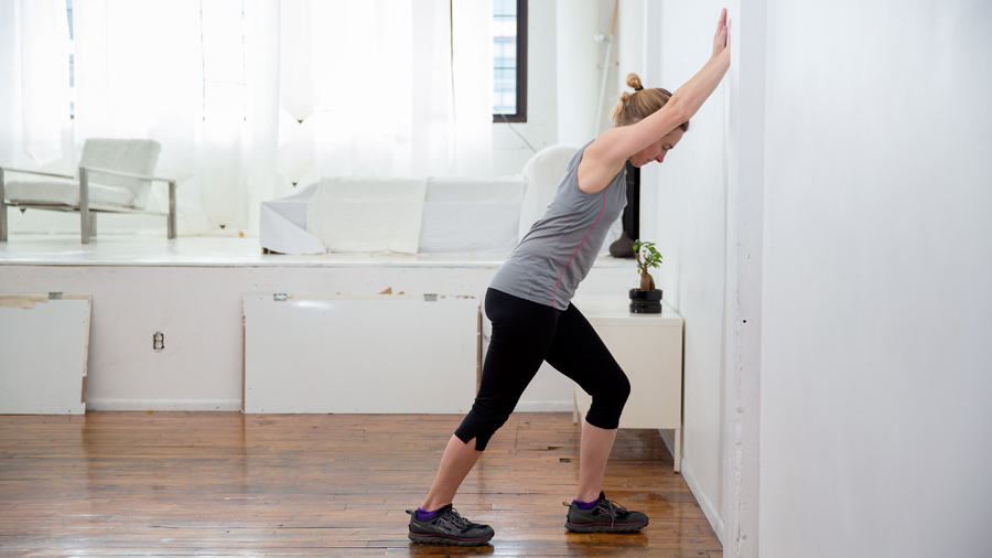 demonstration of a calf stretch against the wall