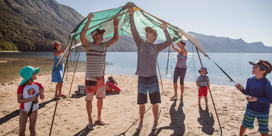 a family in the wearing shades, upf-clothing, and setting up a sunshade to protect from the sun
