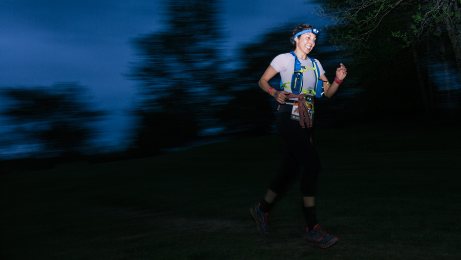 a trail runner running at night by headlamp