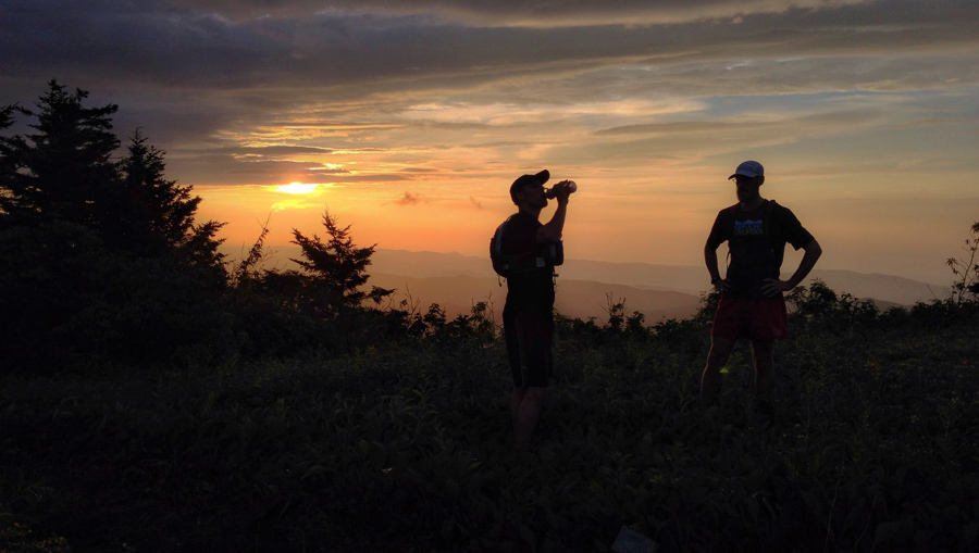 two trail runners taking a hydration break as the sun sets