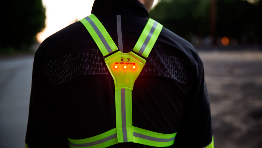 a runner wearing a high-visibility vest as they prepare for a night run