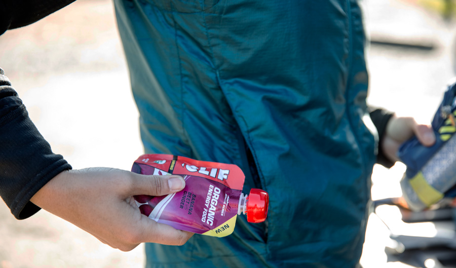 a trail runner placing some running gel in their pocket for the trail