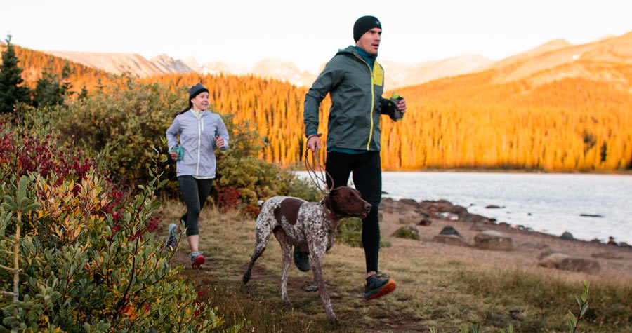 two trail runners on the trail with their dog