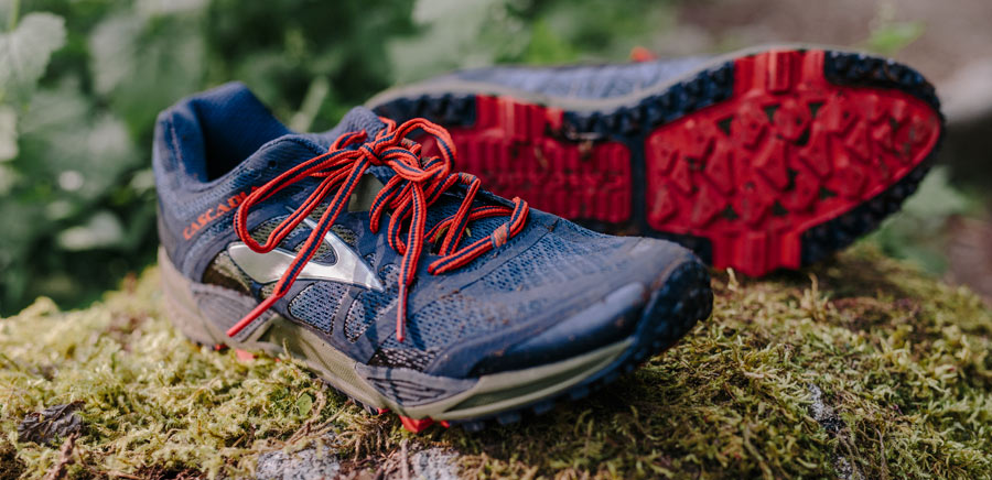 pair of trail running shoes placed on a log, showing shoe uppers and outsoles
