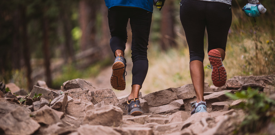 two trail runners running on a rough trail