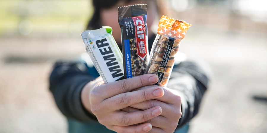 a trio of energy bars in hand