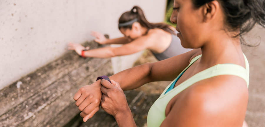 runner checking her pace on her fitness electronic device