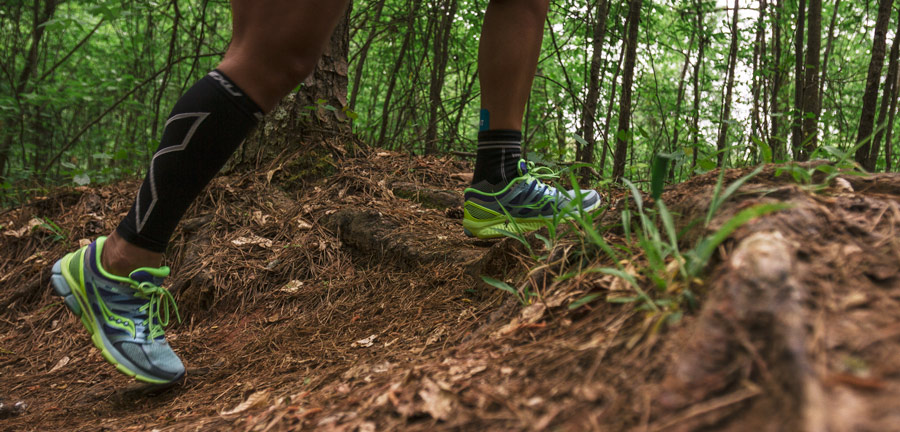 trail runner with compression sleeve on leg