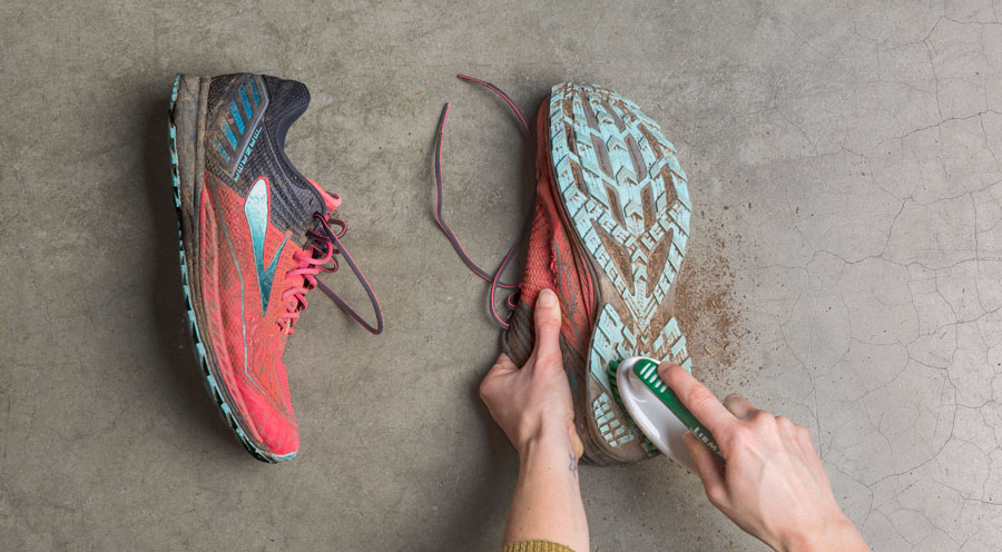 scrubbing dirt off of the outsoles of dirty running shoes