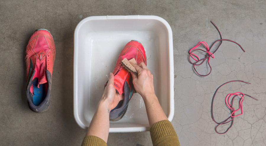 scrubbing the uppers of dirty running shoes with soap and water