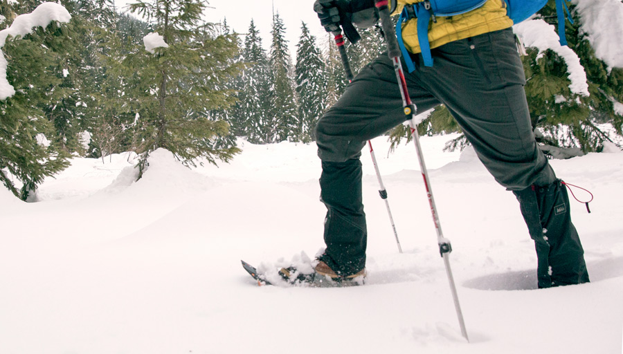 a snowshoer making their way through deep snow with gaiters on