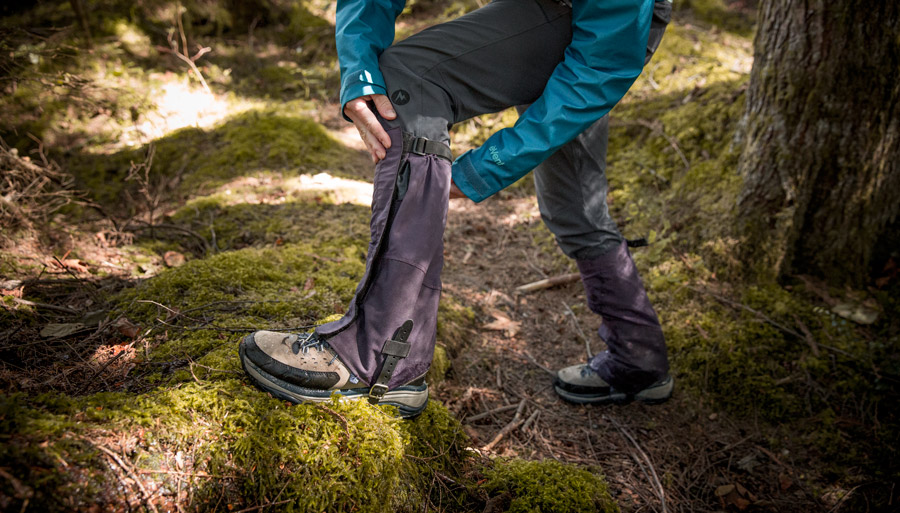 a hiker adjusting their gaiters to fit properly