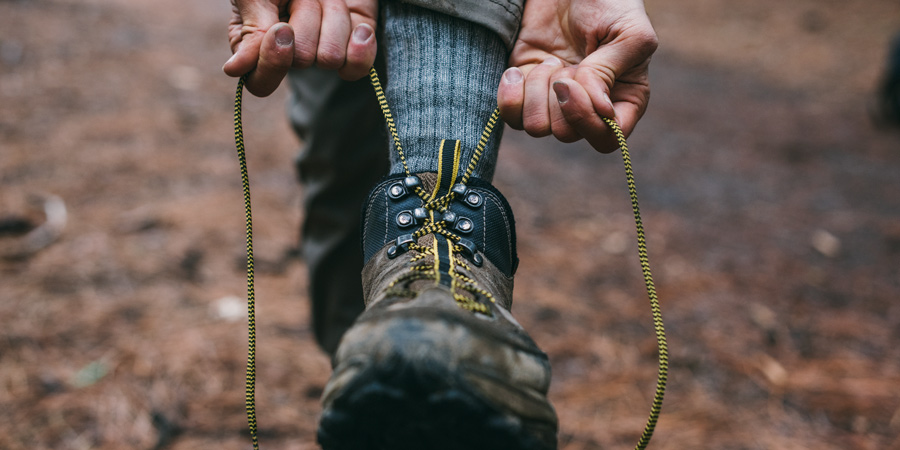 a hiker tying the laces of their hiking boots