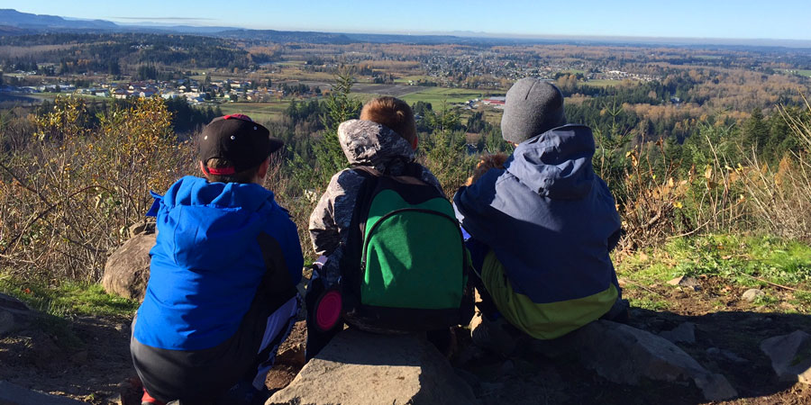 three young hikers looking out of a view point