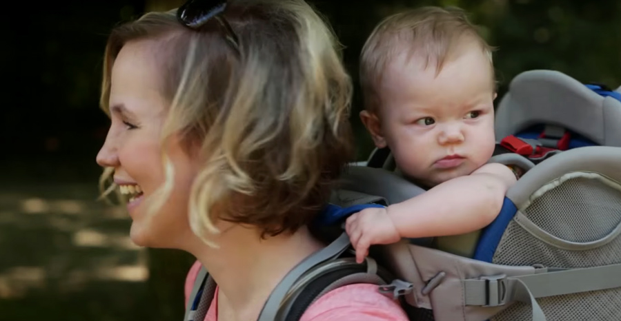 a young infant in a backpack child carrier