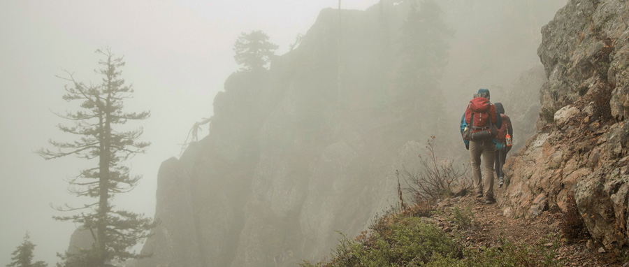 fitnessinf Expert Advice: How to Go Backpacking in the Rain - two backpackers hiking in the rain