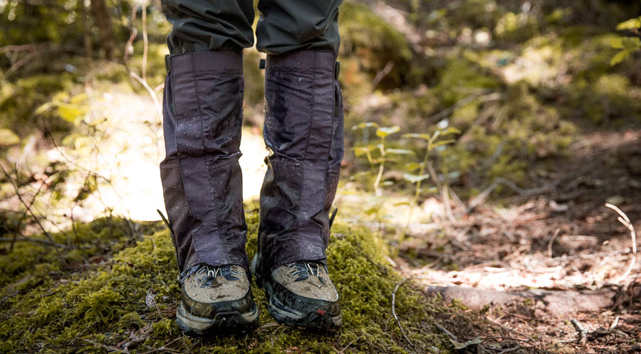 fitnessinf Expert Advice: How to Go Backpacking in the Rain - Backpacker gearing up and wearing gaiters for wet weather on the trail