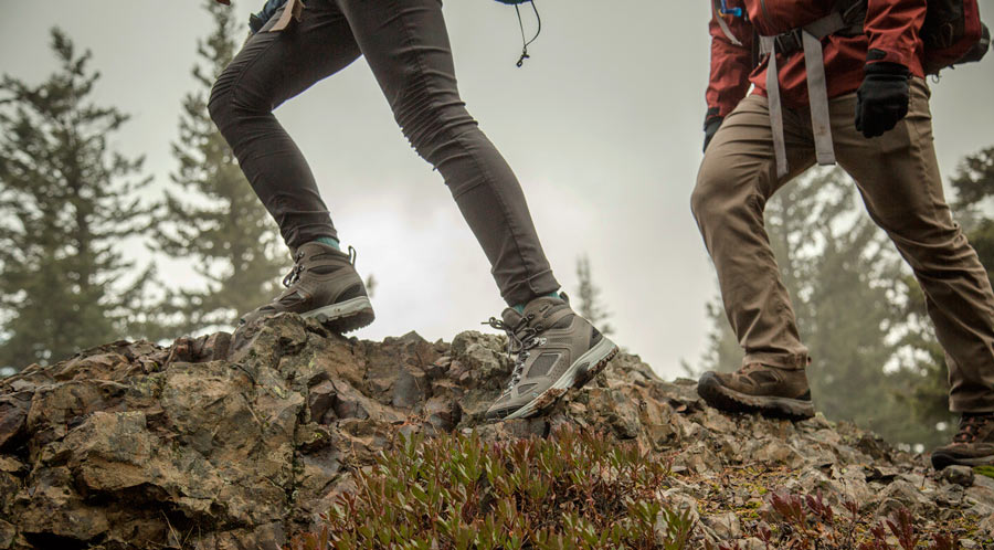 fitnessinf Expert Advice: How to Go Backpacking in the Rain - two backpackers watching their step on steep slippery terrain in the rain