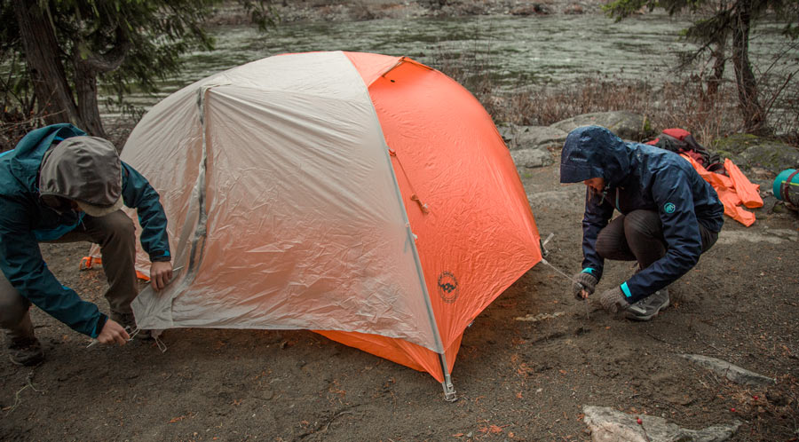 fitnessinf Expert Advice: How to Go Backpacking in the Rain - two backpackers setting up their tent in the rain