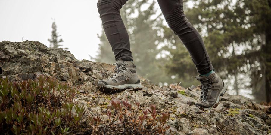 a hiker on a slippery rock surface on a rainy hike