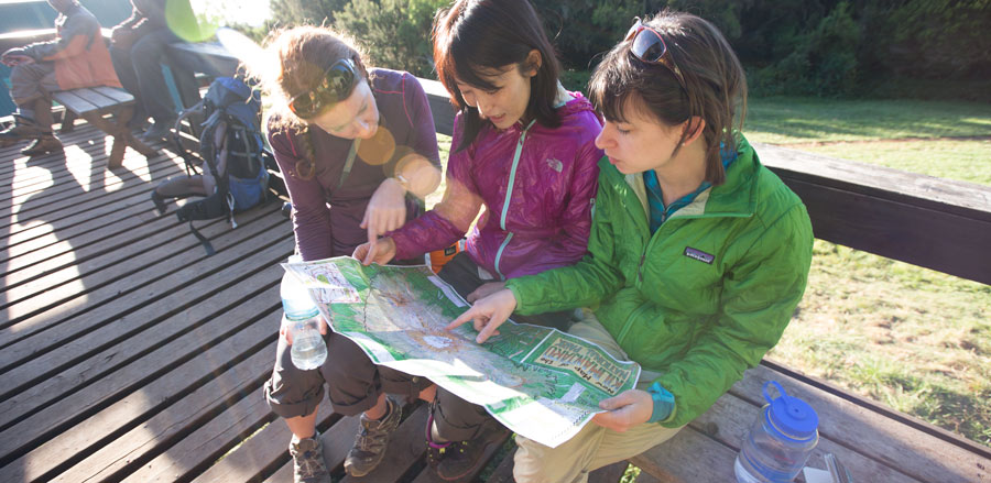 female hikers looking at a map and planning out their backpacking trip