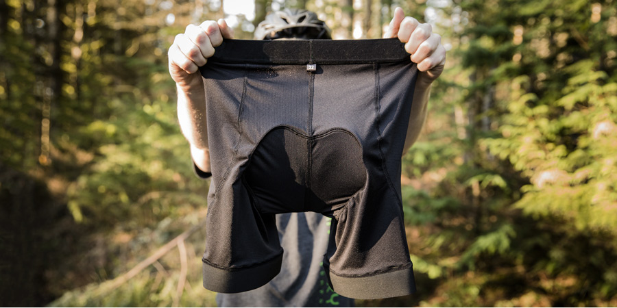 a biker holding up a pair of padded bike shorts