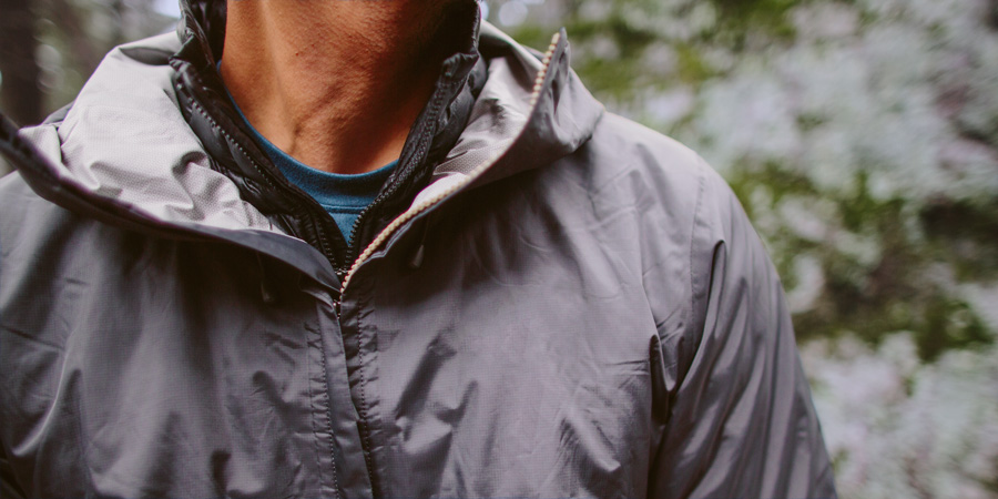 detail of a hiker wearing a base layer, insulating mid layer, and shell layer for a cold day on the trail
