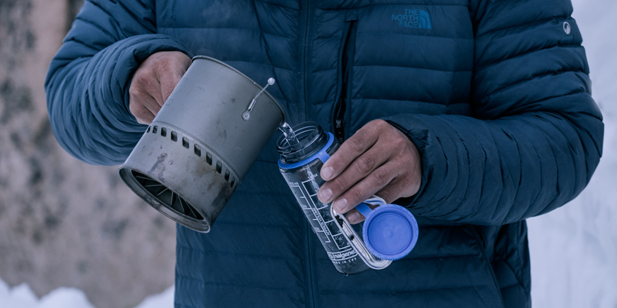 a hiker pouring warm water into a water bottle