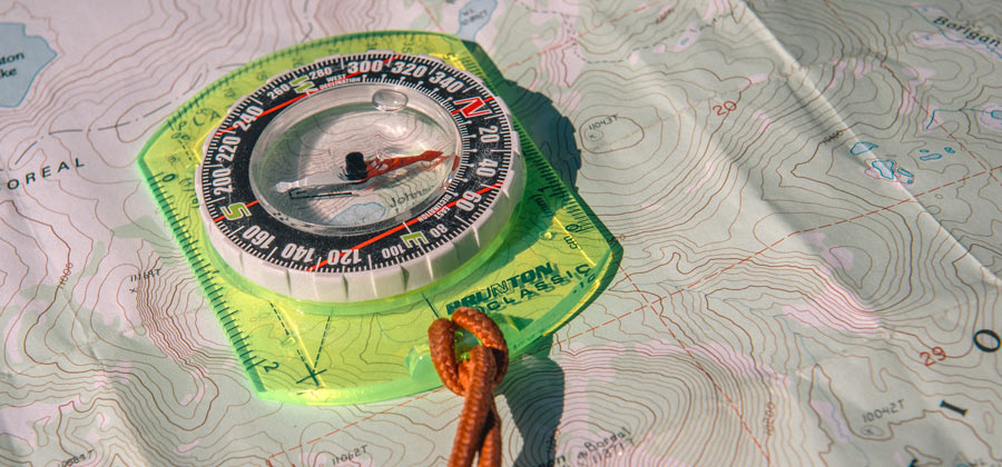 close up of a compass and topographic map