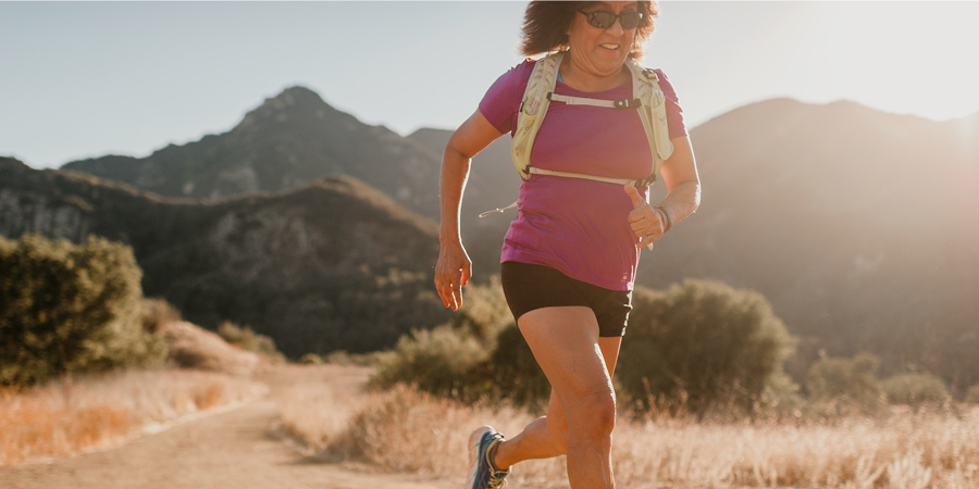 a trail runner running with a running backpack on