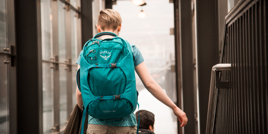a traveler ascending stairs at the station with their travel backpack on