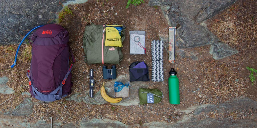 an assortment of gear that could fit into a daypack with a gear capacity between 21-35 liters