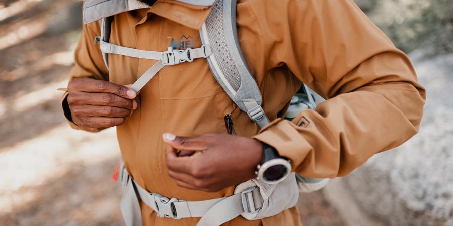 a hiker adjusting their daypack fit